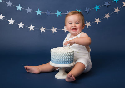 1ST BIRTHDAY PHOTOSHOOT, chester baby photography expert photographs boy smiling on grey and blue birthday cake smash set