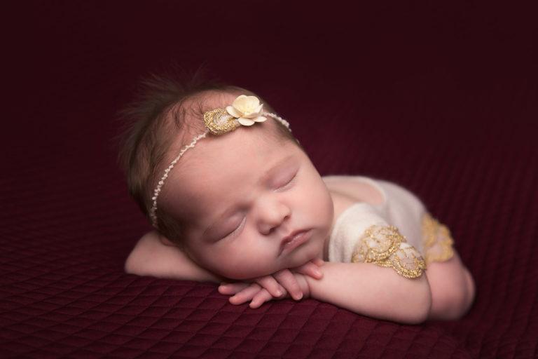 newborn photographer baby girl sleeping on red