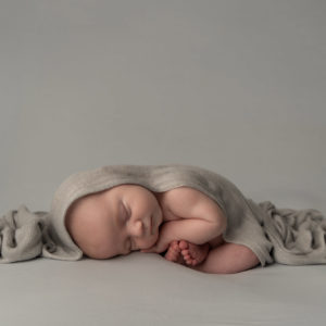 newborn photographer, baby boy sleeping curled up in a grey wrap