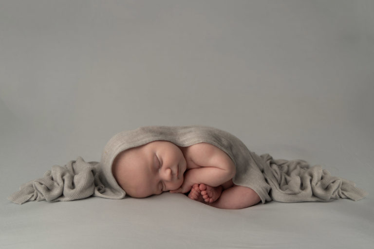 newborn photographer, baby boy sleeping curled up in a grey wrap