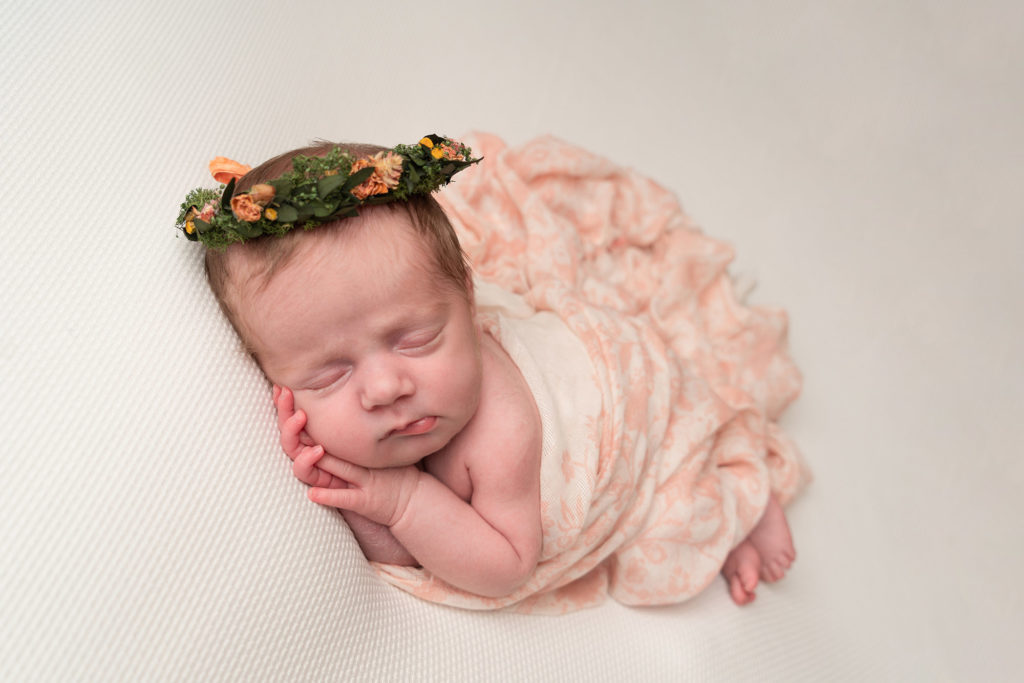 photographing baby at home, little newborn girl in a flower crown sleeping peacefully