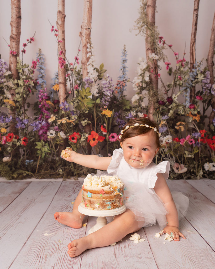 laughing with cake 1st birthday portrait of little girl in white at Cass Davies Photography cake smash studio