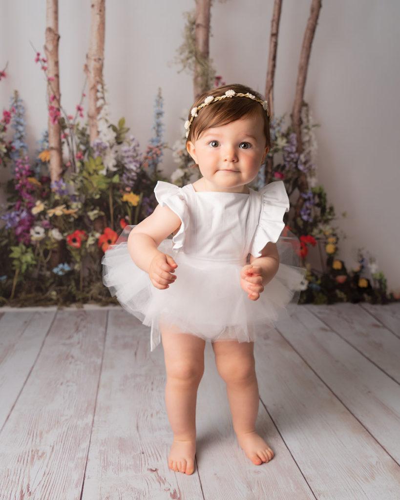 1st birthday portrait of little girl in white at Cass Davies Photography cake smash studio